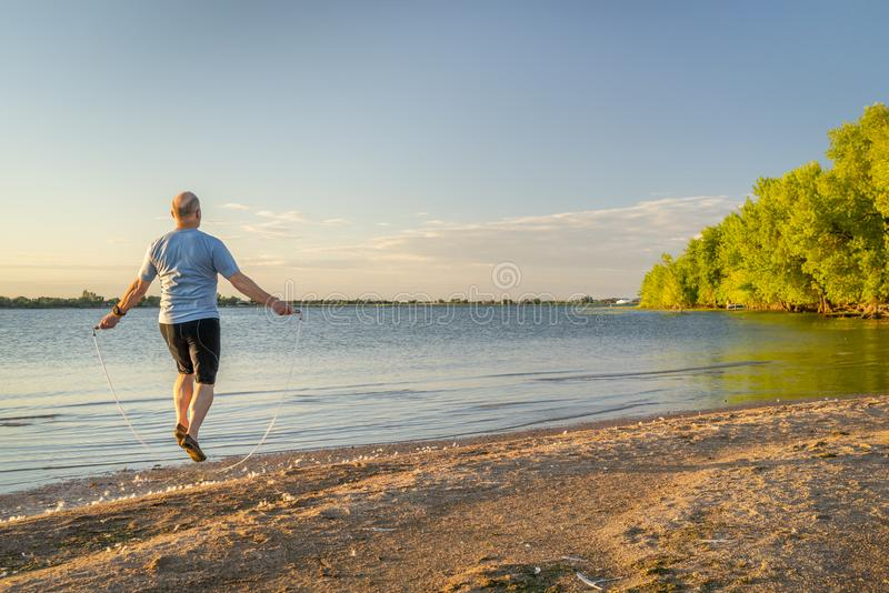 Senior man jumping rope on a beach. Active senior man is jumping a heavy fitness jump rope on a lake beach, Boyd Lake State Park in northern Colorado stock photo