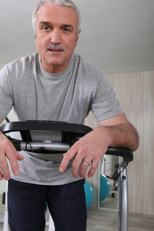 Senior man keeping fit. By cycling at the gym stock images