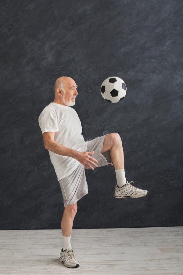 Senior man kicking soccer ball indoors stock photo