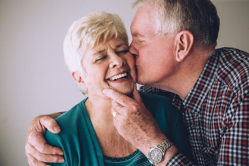 Senior man kissing wife on cheek. Senior men kissing his wife on the cheek. She has her eyes clsoed and is laughing royalty free stock photography