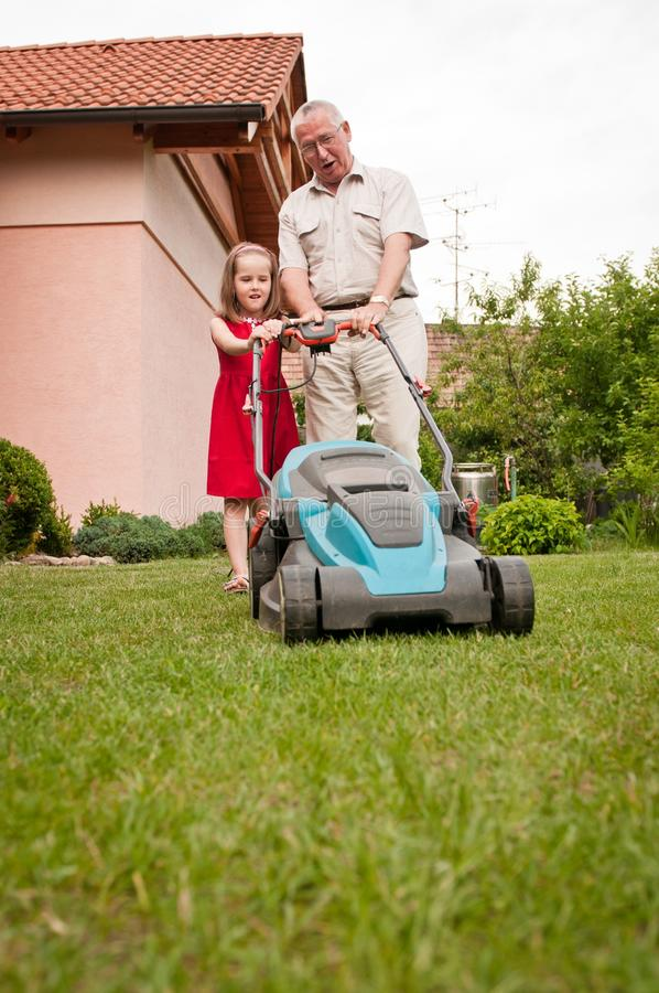 Senior man with lawn mower and child royalty free stock image