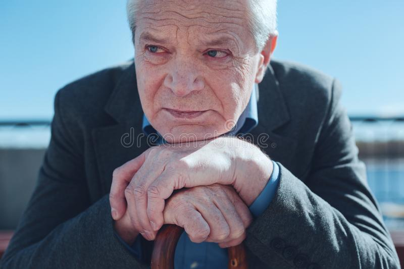 Senior man leaning on cane and thinking of old times stock photo