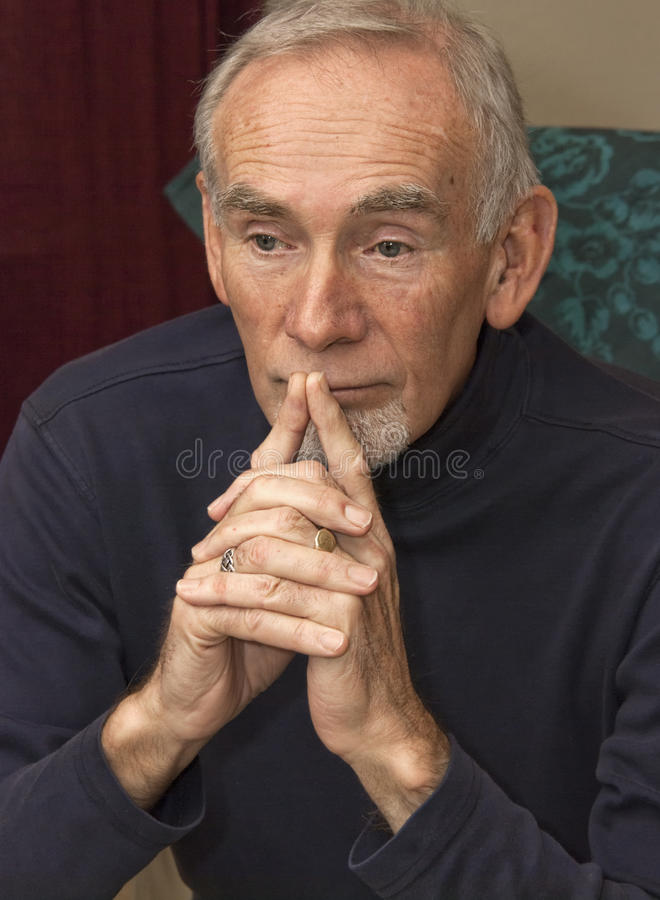 Senior man leaning on his hands, deep in thought