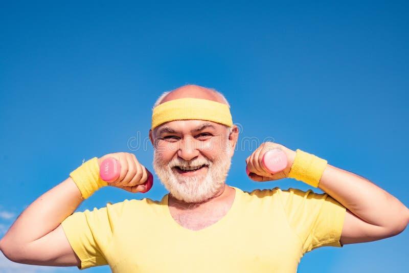 Senior man lifting weights. Lifting dumbbells. Senior fitness man training with dumbbells isolated on blue background stock photo