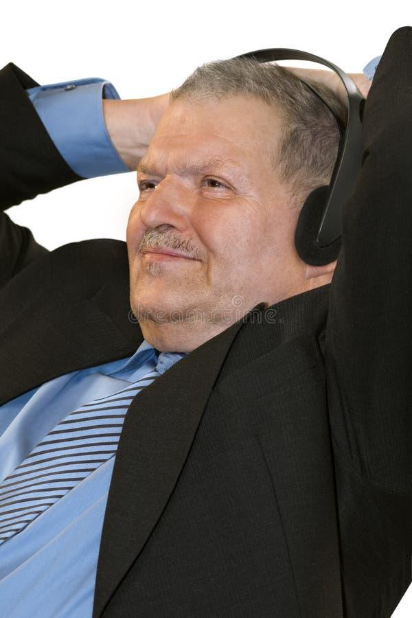 Senior man listening to music stock photo