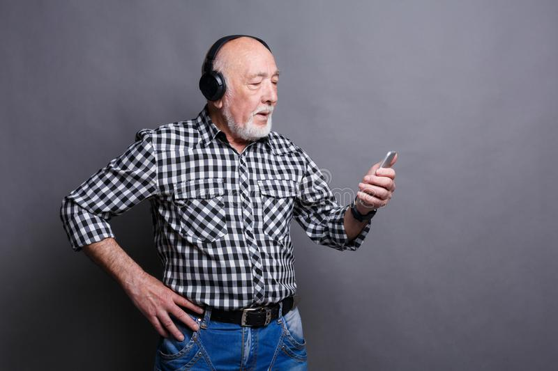 Senior man listening to music with headphones stock image