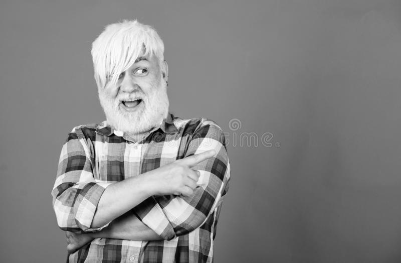 Senior man with long bangs and beard. Mature hipster unusual appearance. Subculture and lifestyle. Barbershop and royalty free stock photo