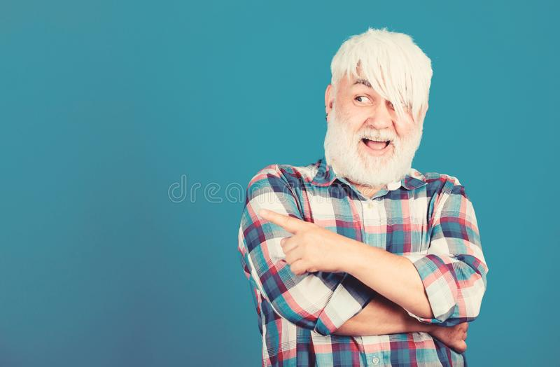 Senior man with long bangs and beard. Mature hipster unusual appearance. Subculture and lifestyle. Barbershop and stock photos