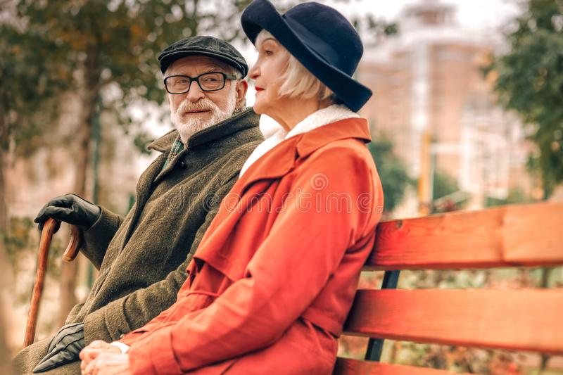 Senior man looking lovingly at his wife sitting on bench in park royalty free stock photo