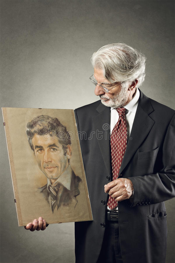 Senior man looking at paint of himself younger royalty free stock photography