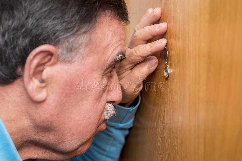 Senior man looking through peephole.  stock photo
