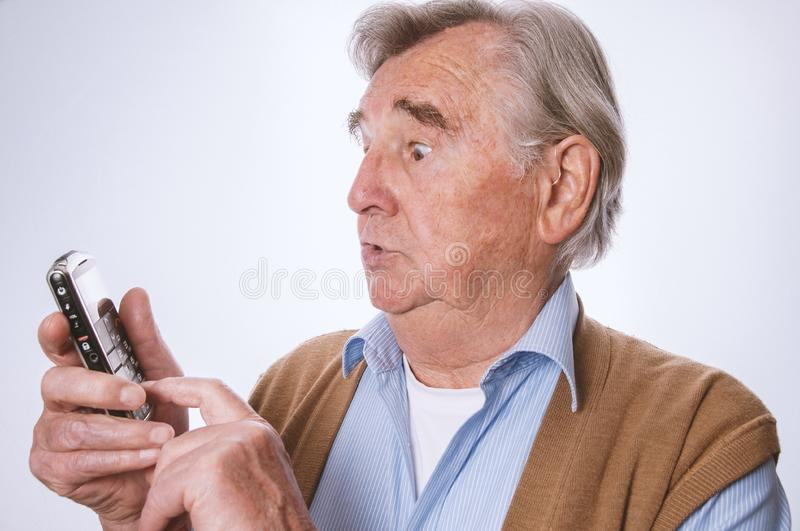 Senior man looking surprised and using his mobilphone. Modern senior using his mobilphone and looking surprised-  on white background stock photography