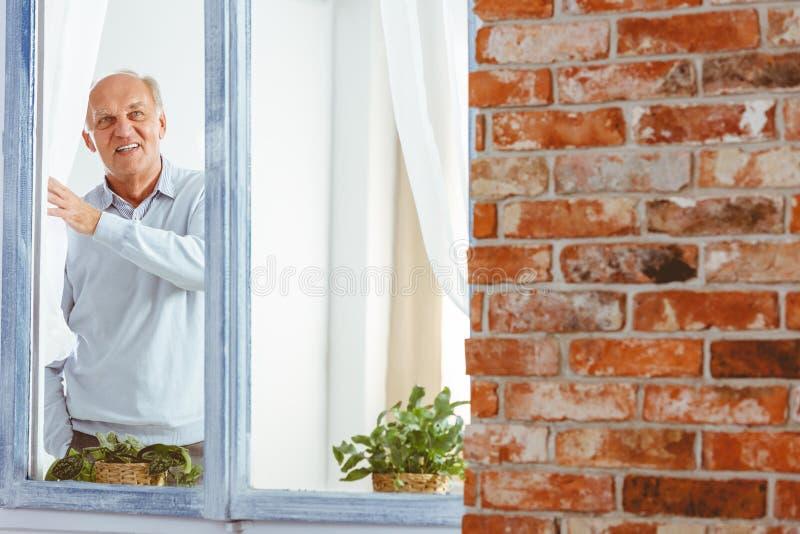Senior man looking through window stock images