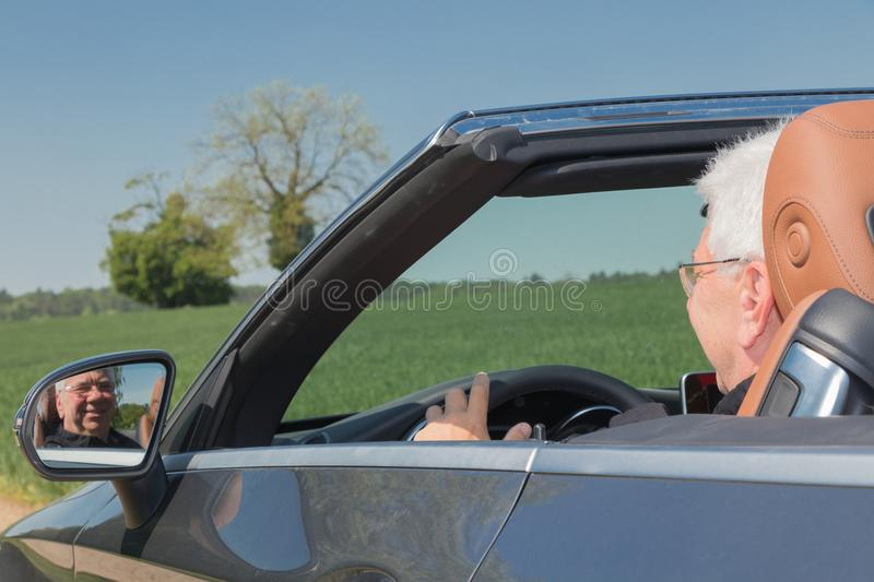 Senior man in a sports car royalty free stock images