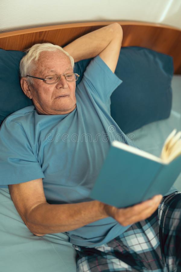 Senior man lying on bad and reading book royalty free stock images