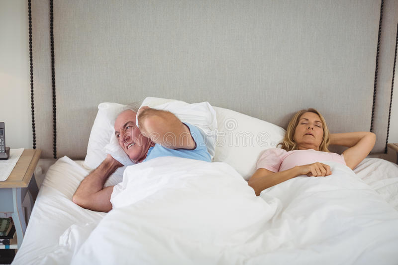 Senior man lying on bed and covering his ears with pillow stock photography