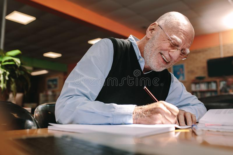 Senior man making notes in classroom royalty free stock photo