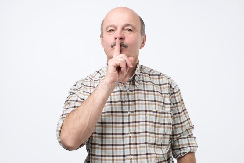 Senior man making silence gesture, keep it in secret stock photography