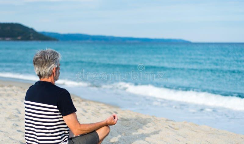 Senior man meditating on the beach. Summer vacation workout stock photo