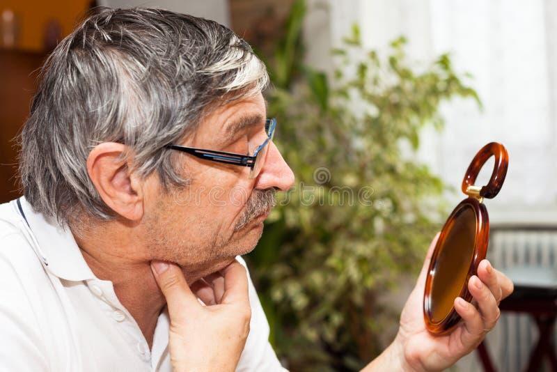 Senior man with mirror. Senior man checking his double chin in mirror royalty free stock photo