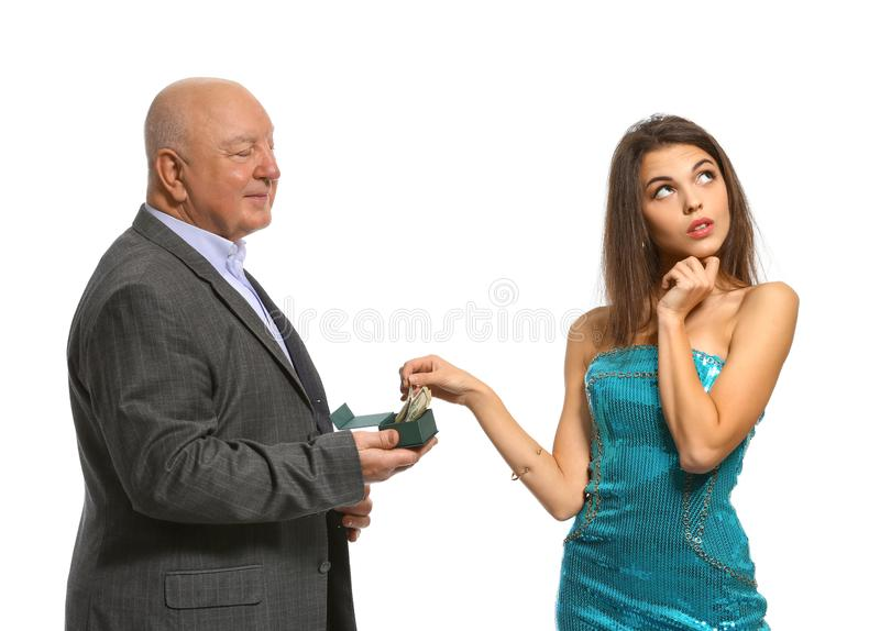 Senior man with money proposing to young woman on white background. Marriage of convenience. Senior men with money proposing to young women on white background royalty free stock image