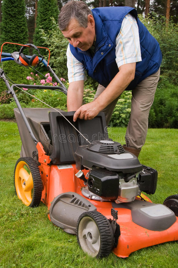 Senior man mowing the lawn. In the garden stock photography