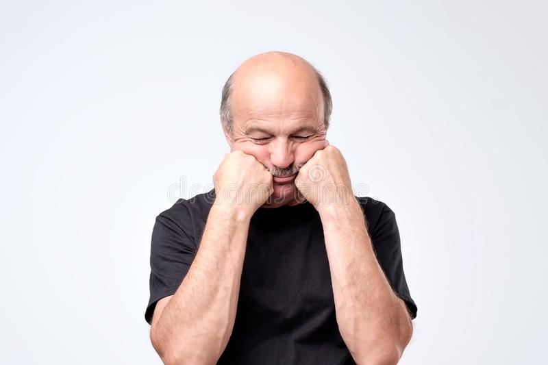 Senior man with mustache covering face with both hands, feeling stressed ou. T stock photo