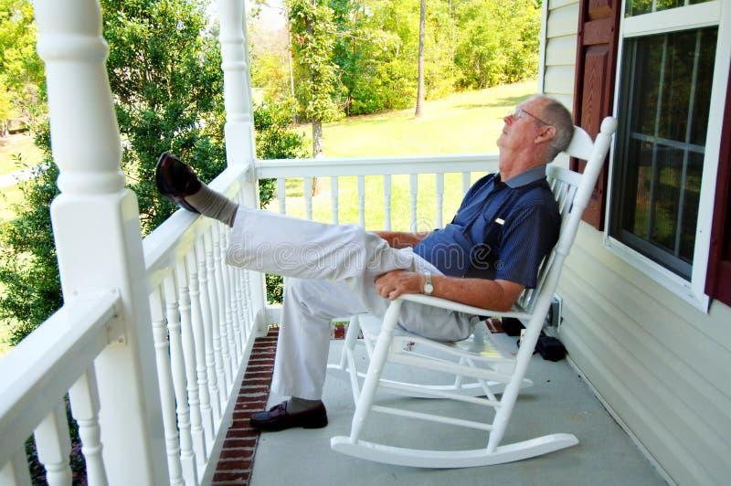 Senior man naps on front porch royalty free stock photography
