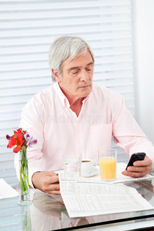 Download Senior Man With Newspaper And Cell Stock Photo - Image: 23248900
