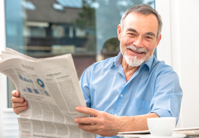 Senior man with a newspaper. Happy senior man at breakfast with newspaper stock images
