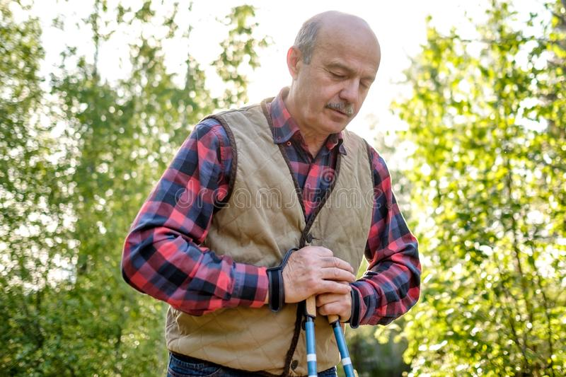 Senior man nordic resting after nordic walking in park. stock photos