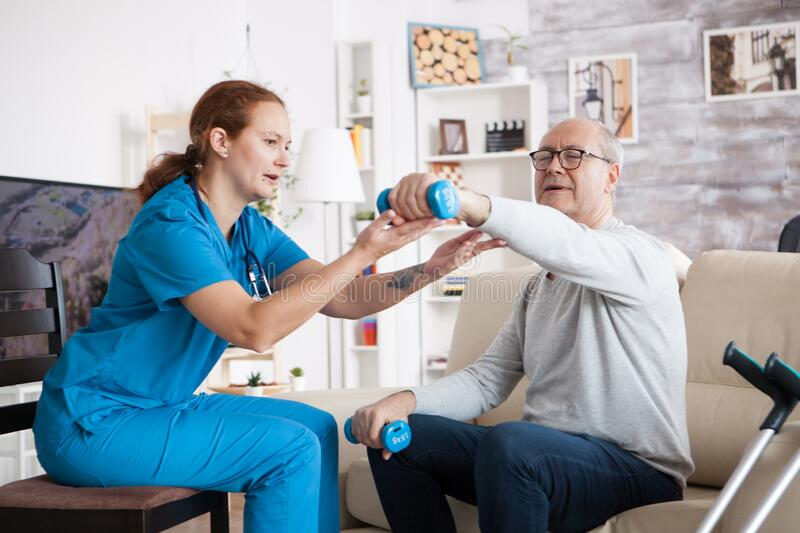 Senior man in nursing home with doing physical therapy. Senior men in nursing home with doing physical therapy with help from nurse using dumbbells stock images