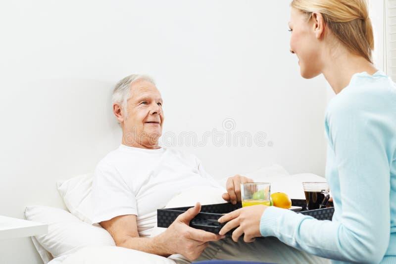 Senior man in nursing home having breakfast. Senior men in nursing home having breakfast in bed stock photo