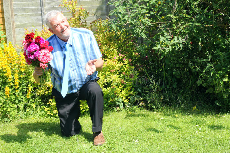 Senior man on one knee proposing. A senior man kneeling down proposing marriage. He has a bunch of flowers in one hand and holding other hand to ask royalty free stock photo