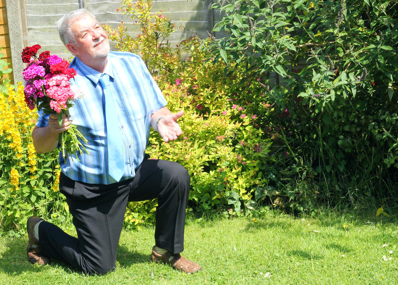 Senior man on one knee proposing, side view. A side view of a senior man kneeling down proposing marriage. He has a bunch of flowers in one hand royalty free stock photography