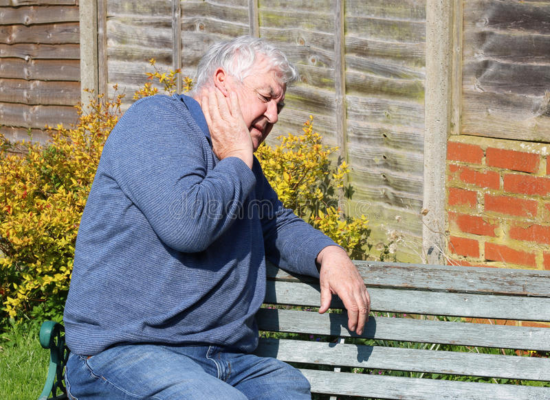 Senior man with painful injured neck. A senior man in agony with a painful neck either injured or sick royalty free stock photography