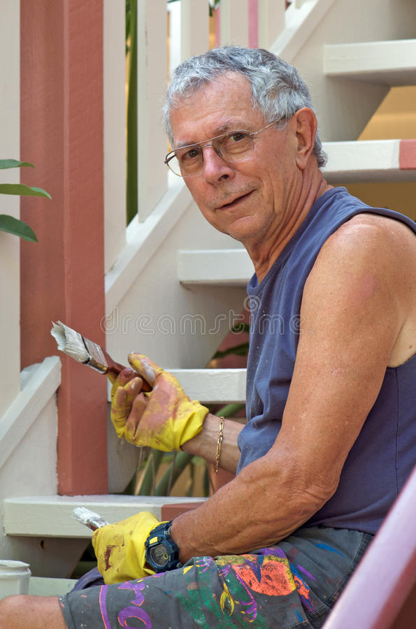 Senior man painting home. Senior man painting the stairs of his wooden house stock photography