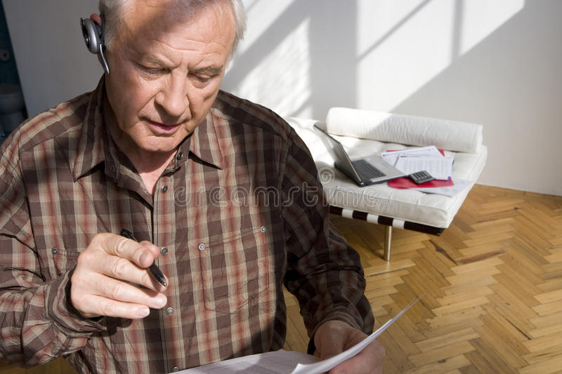 Senior man with paperwork and hands-free device stock images