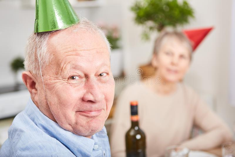 Senior man with party hat stock photography