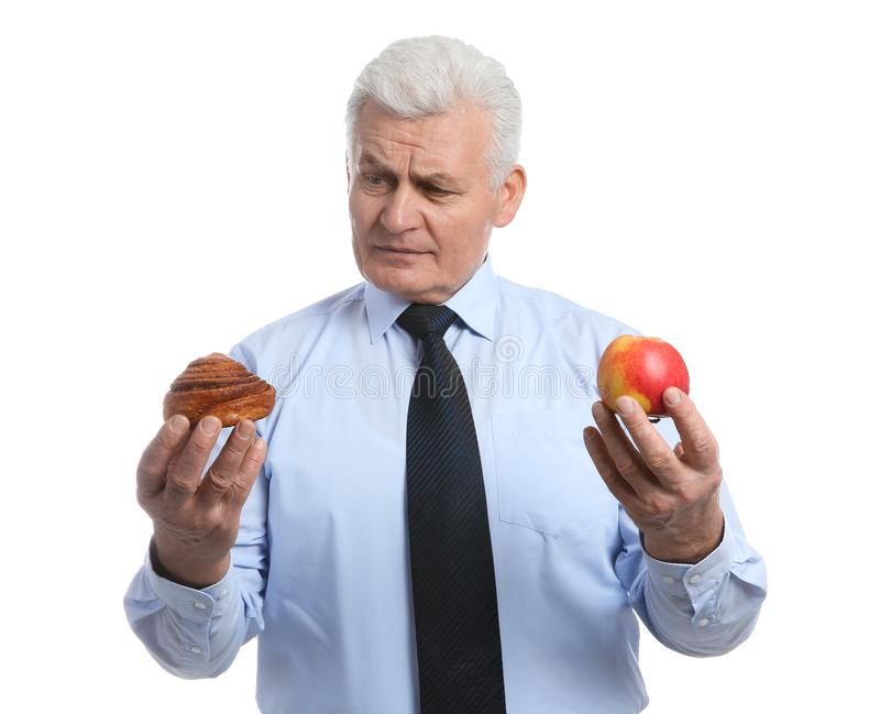 Senior man with pastry and apple on white. Diabetes diet royalty free stock image
