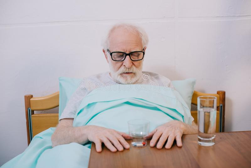 Senior man patient in clinical bed looking royalty free stock images
