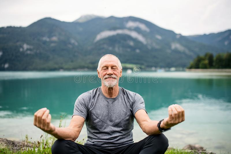 A senior man pensioner sitting by lake in nature, doing yoga exercise. stock photos