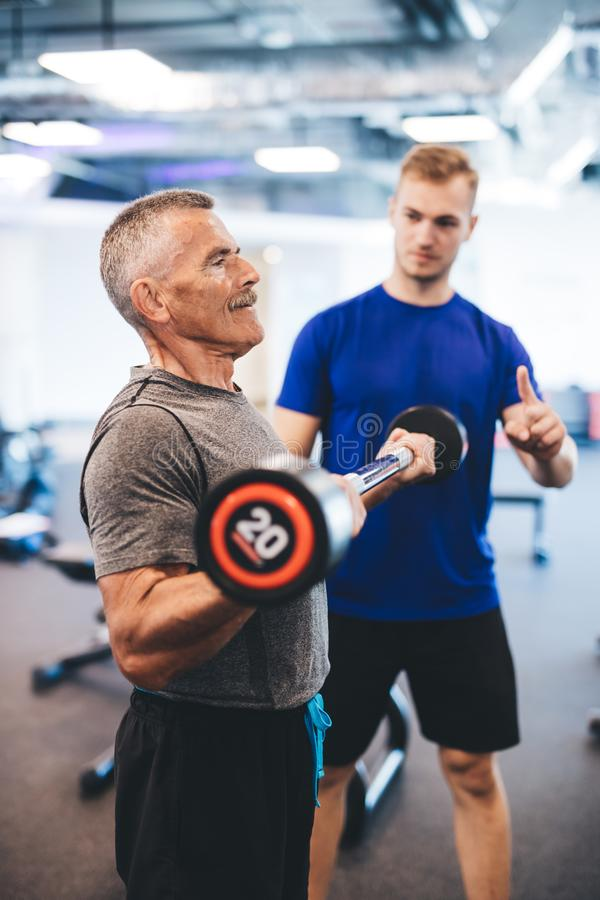 Senior man and personal trainer at the gym. stock photos