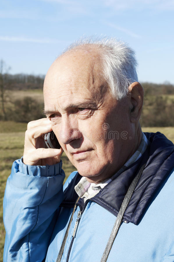 Senior man with phone. In the nature in Autumn royalty free stock photo