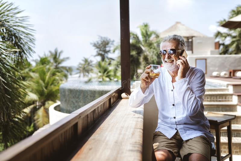 Senior man on the phone having a drink stock images