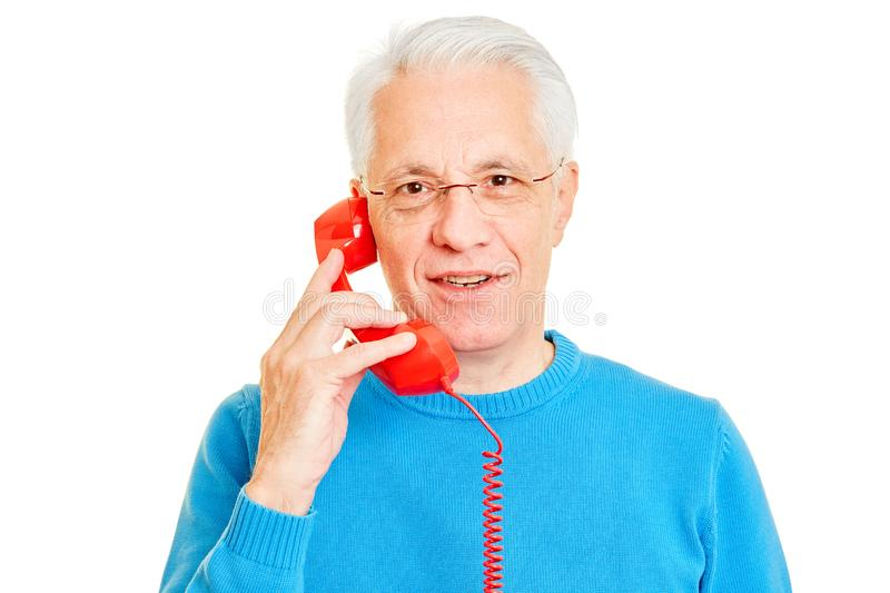 Senior man is on the phone with an old telephone. Senior man is on the phone with an old red phone royalty free stock photography