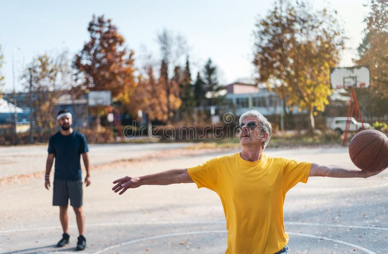 Senior man playing basketball with his son in a park stock image