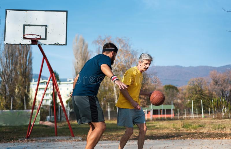 Senior man playing basketball with his son in a park stock images