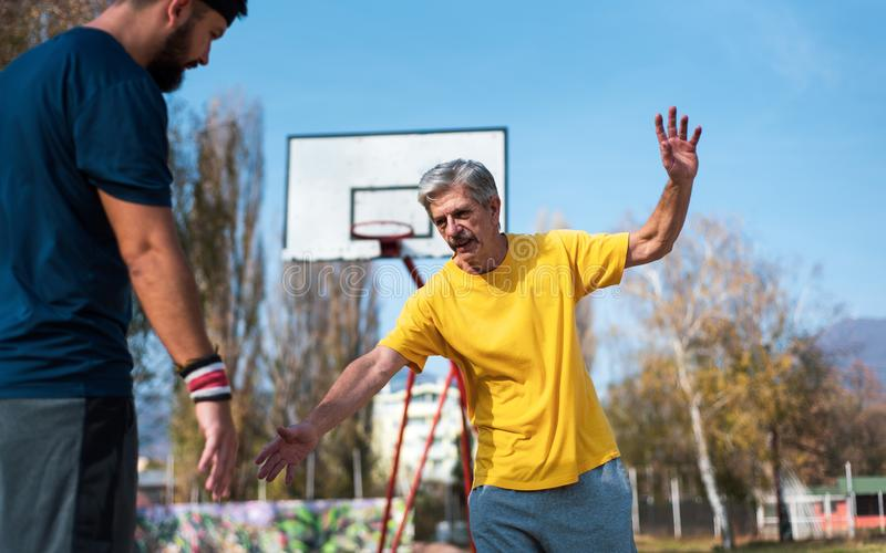 Senior man playing basketball with his son in a park stock photography