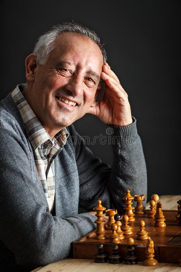 Senior man playing chess. On black background royalty free stock photos